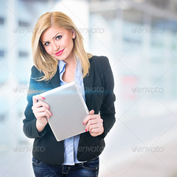 Attractive businesswoman in front of office holding digital tablet - Stock Photo - Images