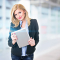 Attractive businesswoman in front of office holding digital tablet - PhotoDune Item for Sale