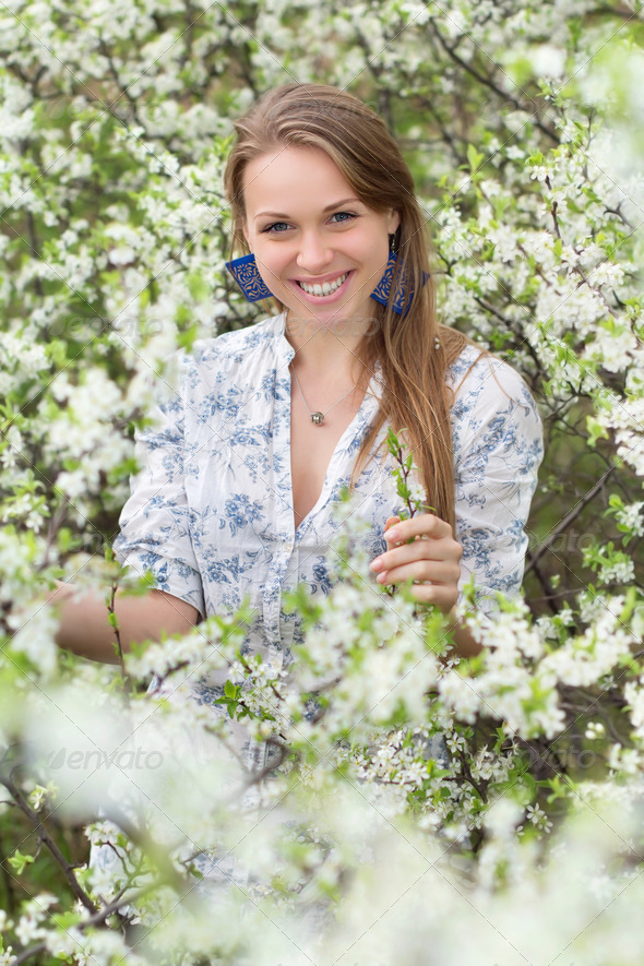 Smiling blonde in blooming garden - Stock Photo - Images