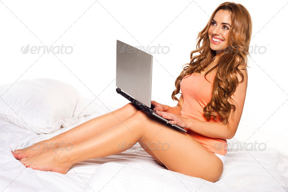 Woman relaxing on her bed with a laptop - Stock Photo - Images