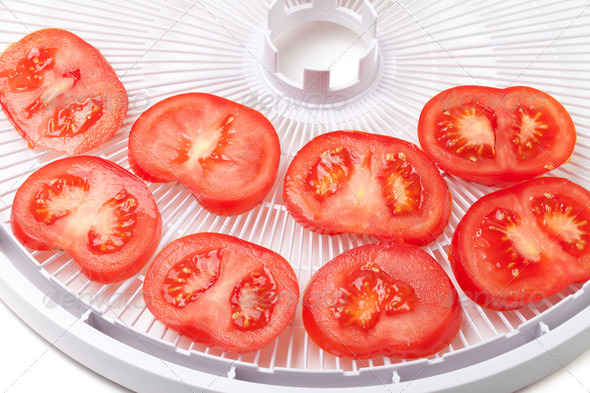 Fresh tomato on food dehydrator tray, ready to dry - Stock Photo - Images