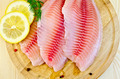 Fillets tilapia with lemon on a round board - PhotoDune Item for Sale