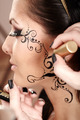 Brunette having applied face tattoo by makeup artist - PhotoDune Item for Sale