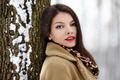 Beautiful brunette leaning on a tree trunk in the winter - PhotoDune Item for Sale