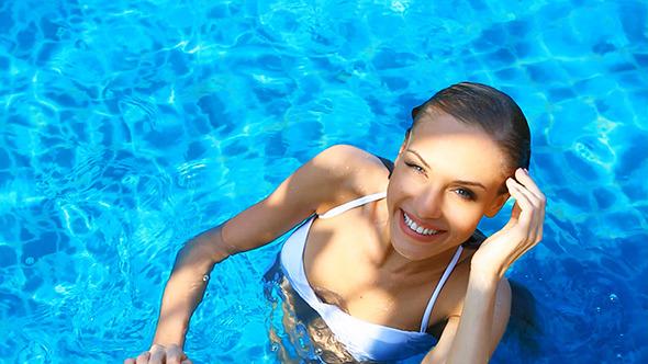 Beautiful Girl In Bikini Relaxing In Swimming Pool By