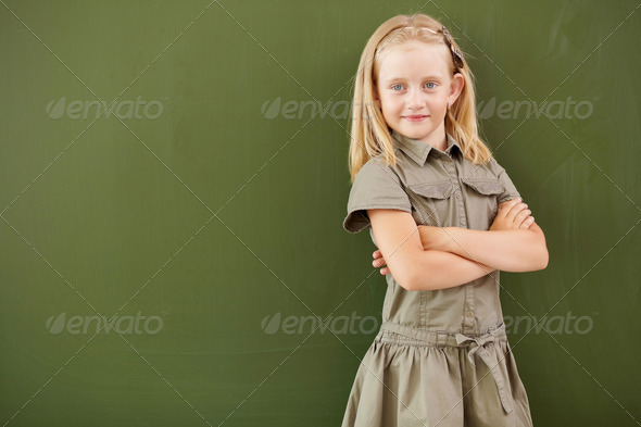 Scoolgirl standing near blackboard - Stock Photo - Images