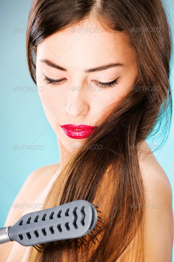 woman with long hair holding comb - Stock Photo - Images