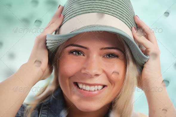 Woman holding her hat in the rain - Stock Photo - Images