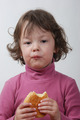 A  young girl eating a bun - PhotoDune Item for Sale