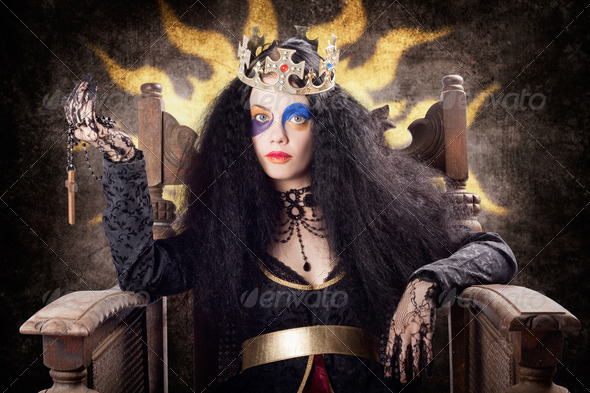 Storybook queen jester holding religious cross - Stock Photo - Images