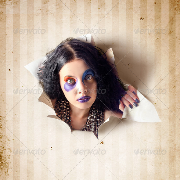 Beautiful female jester breaking out of wallpaper - Stock Photo - Images