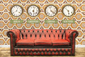 Retro chesterfield sofa with world time clocks on a wall - PhotoDune Item for Sale