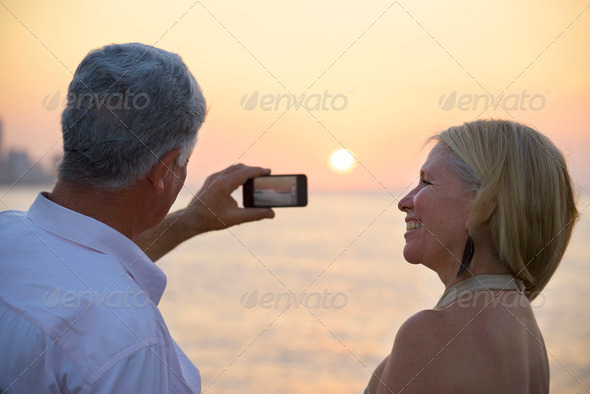 Senior man and woman using mobile phone to take photo - Stock Photo - Images