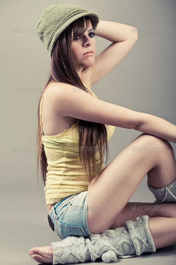 Side pose of beautiful model sitting with green cap - Stock Photo - Images