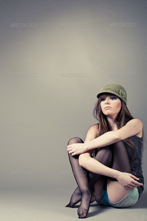 Beautiful young girl sitting with her knees pulled up - Stock Photo - Images
