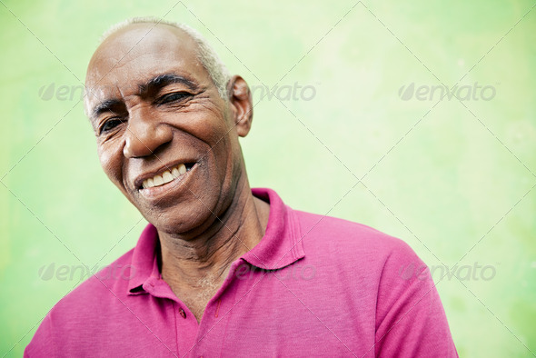 Portrait of elderly black man looking and smiling at camera - Stock Photo - Images
