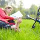 Girl cyclist on a halt reads lying in fresh green grass barefoot - PhotoDune Item for Sale