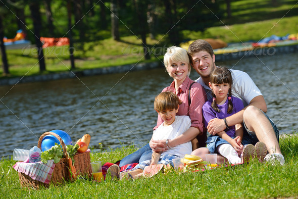 Happy family playing together in a picnic outdoors - Stock Photo - Images