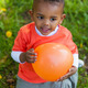 Outdoor portrait of a cute young  little black boy playing with - PhotoDune Item for Sale