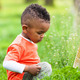 Outdoor portrait of a cute young  little black boy playing outsi - PhotoDune Item for Sale