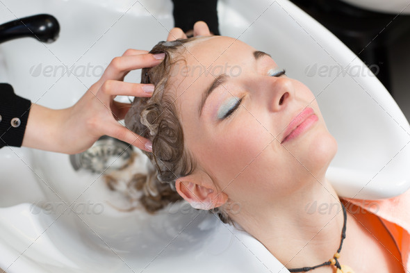 hairstylist washing customers hair - Stock Photo - Images