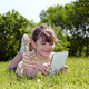 little girl lying on grass and play with tablet pc - PhotoDune Item for Sale