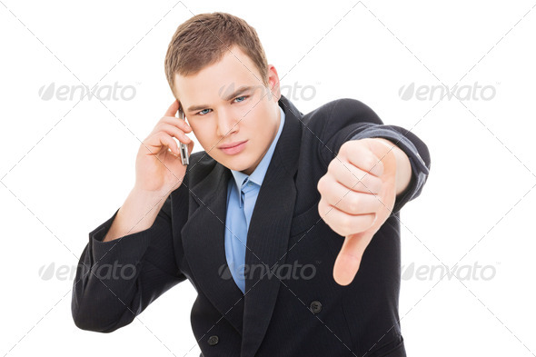 Young businessman speaking on smartphone showing thumb down - Stock Photo - Images