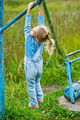 little girl hanging on old exercise equipment - PhotoDune Item for Sale