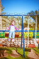little girl on swing in children's city park - PhotoDune Item for Sale