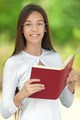 Smiling teenage girl reading red book - PhotoDune Item for Sale