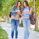 Young Adult Mixed Race Twin Sisters Sharing Cell Phone Experience Outside. - PhotoDune Item for Sale
