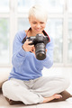 Female photographer with DSLR at home sitting on the floor - PhotoDune Item for Sale