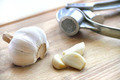 Garlic and garlic press on wooden cutting board - PhotoDune Item for Sale