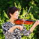 Senior woman focused with eyes closed while playing music outdoo - PhotoDune Item for Sale