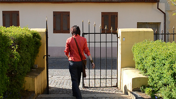 Woman Exits Yard Throught Iron Gate