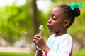 Outdoor portrait of a cute young black girl blowing a dandelion - PhotoDune Item for Sale