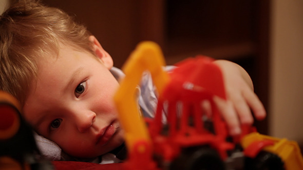 Two Year Old Boy Plays With Toy Trucks