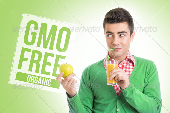 Young man with healthy GMO free juice and apple - Stock Photo - Images