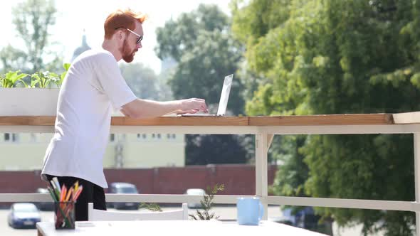 Download Young Man Typing on Laptop, Standing in Balcony Outdoor nulled download