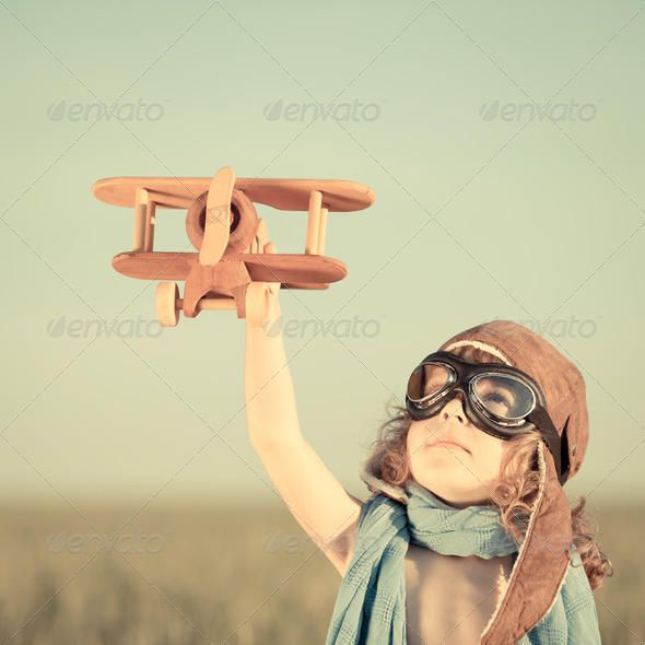 Happy kid playing with toy airplane - Stock Photo - Images