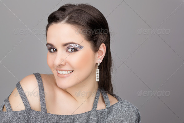Elegant young woman wearing sparkling dress and makeup - Stock Photo - Images
