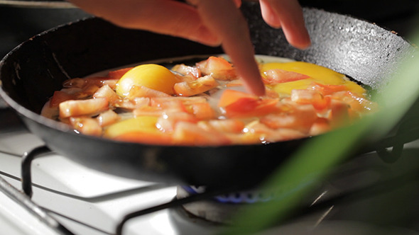 Egg Frying In A Pan Adding Tomato Slices