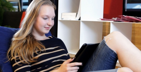Young Female Student Using Tab in Campus Rest Room