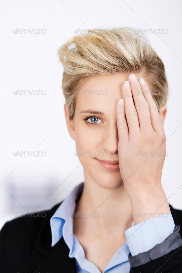 Businesswoman Hiding Eye With Hand In Office - Stock Photo - Images