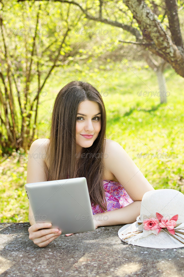 Happy young woman with tablet computer in the park - Stock Photo - Images