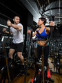 elliptical walker trainer man and woman at black gym
