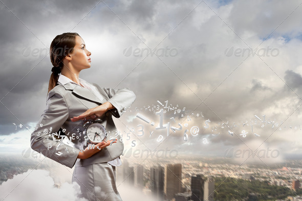Businesswoman holding alarmclock - Stock Photo - Images