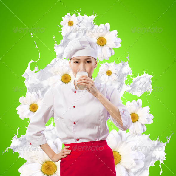 Asian female cook against milk splashes - Stock Photo - Images