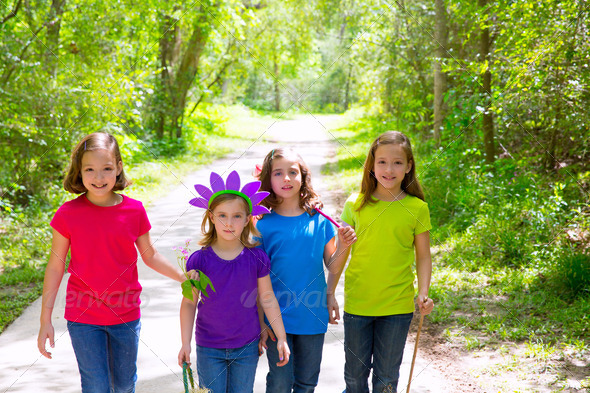 Friends and sister girls walking outdoor in forest track - Stock Photo - Images