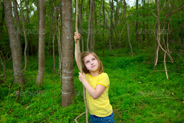 Happy girl playing in forest park jungle with liana - Stock Photo - Images